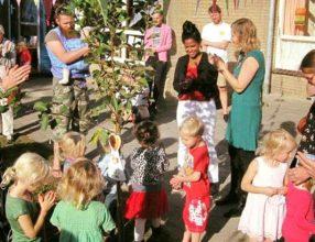 Kinderen planten appelboom met directeur ter ere van opening peuteropvang Gouden Poort